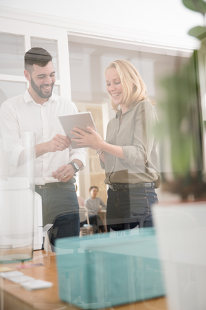 Man and woman laughing as she holds a pc tablet they are both looking at, he is pointing at the tablet