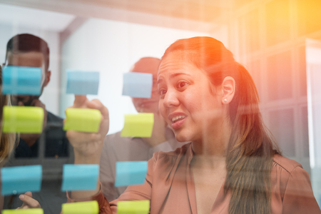Woman looking at a clear glass window scowling at the blue and green sticky notes that are pasted on the window Stock Photo