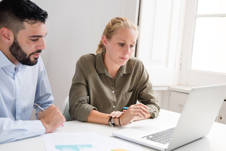 Business team working in an office at a desk with a laptop in front of them, they are concentrating