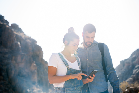 Couple standing in the mountains and looking down at a cell phone and pointing at the screen