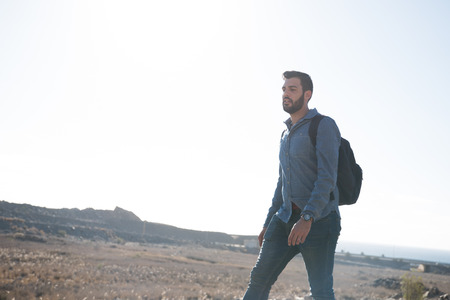 Man dressed in jeans and wearing a backpack striding confidently as he walks through the desert
