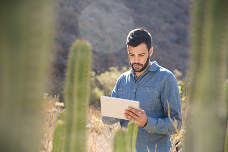 Close up of a man using a pc tablet standing near cactus and a mountain side