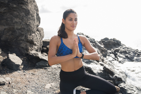 Woman with her hands clasped in front of her as she squats on a rocky beach