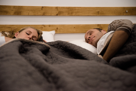 Couple lying in a bed, they both have their eyes closed and are sleeping