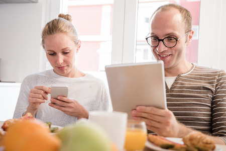 Couple looking down at their technology as they sit at a table and eat a breakfast