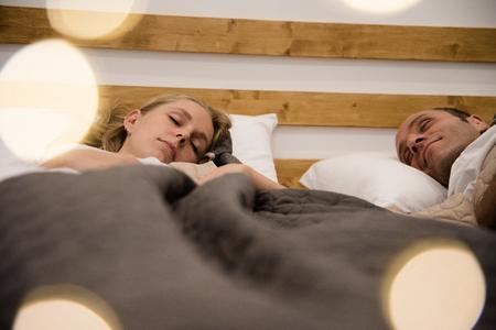 寝るときに目を閉じてベッドに横たわっているカップル