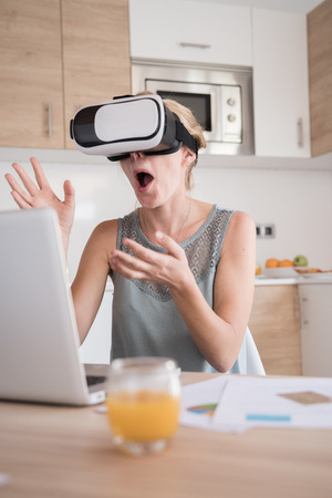 Woman is gasping and laughing, her hands are in the air in front of her as she is wearing virtual reality glasses Stock Photo