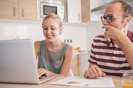 Couple sitting at a table in a kitchen with a laptop in front of them as they both smile and look at the screen