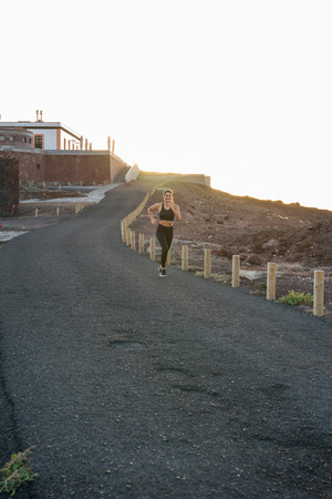 Long distance shot of a woman running on a road next to a low fence in the sunset