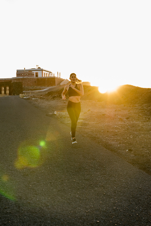 Woman running along a road as the sun rises in the background in the sunset Stock Photo