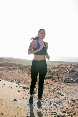 Young woman running in the desert wearing dark running clothes and shoes 免版税图像 - 106238349