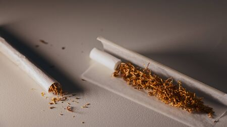 Isolated and slightly illuminated rolling tobacco cigarettes