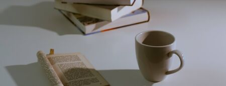 Slightly high angle view of teacup next to reading book on a white desk. Dim lighting