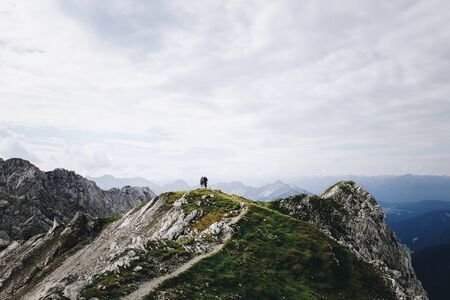 Silhouette of two people on a mountain peak in the Alps Imagens