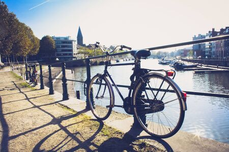 Parking bicycle at the metal fence of a water canal Foto de archivo