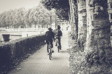 Back of two cyclists in black and white