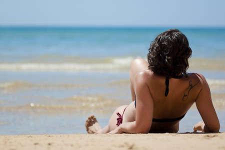 sicily: woman taking sun on the beach