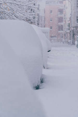 Several cars in the street in Madrid covered in snow. More than 30 cm of snow. Filomena Storm.