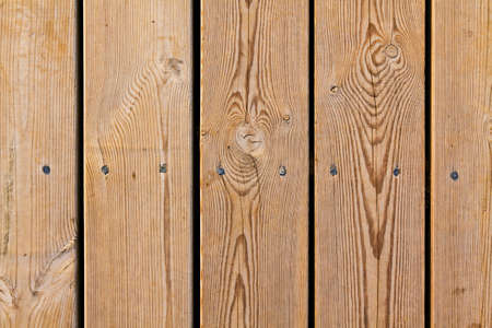 Wooden planks with knots and nails in a row photo
