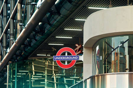 London underground tube station sign with modern building