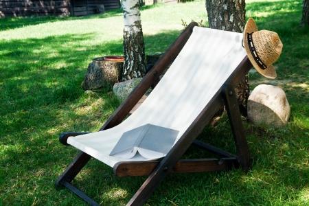 Offenes Buch und Strohhut auf dem Liegestuhl und Gras