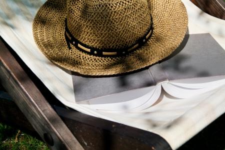 straw hat: Open book and straw hat on deckchair