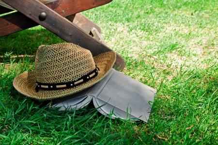 Open book and straw hat on grass with deckchair Standard-Bild