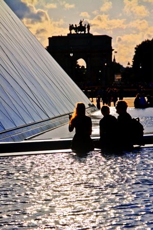 louvre pyramid: Tourists sitting on Louvre fountain near Louvre Pyramid in Paris Editorial