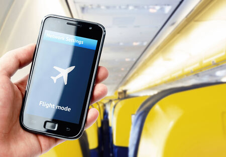 Hand holding smartphone inside the plane with flight mode activated Stock Photo