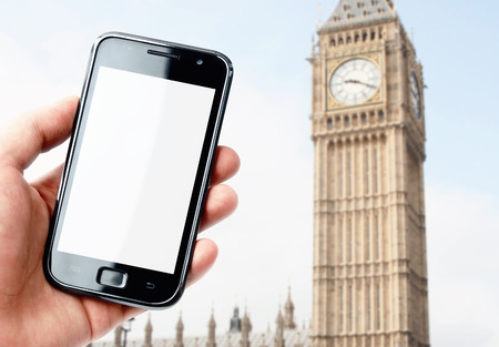Hand holding blank screen smartphone with London city view photo