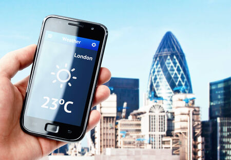 forecast: Hand holding smartphone with weather on the screen in London