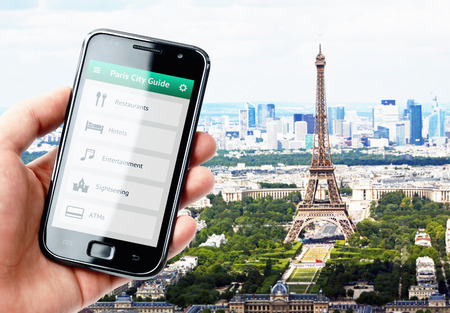 Hand holding smartphone with city guide on the screen in Paris photo