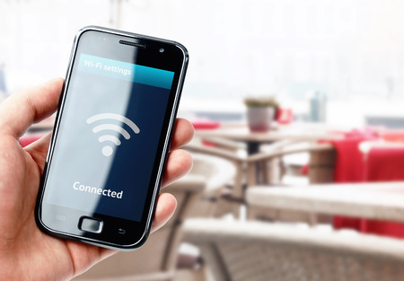Ruka držící smartphone s wi-fi připojením na obrazovce v kavárně