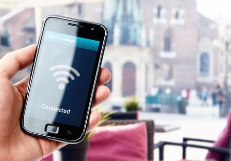 Mão segurando o smartphone com conexão wi-fi na tela no café