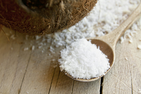 desiccated: Desiccated white coconut with wooden spoon