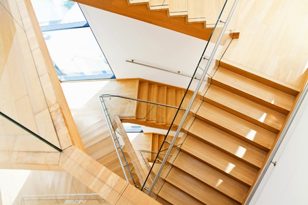 Modern architecture interior with elegant wooden stairs and glass balustrade