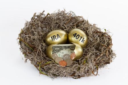 황금 달걀로 가득 찬 둥지에 현금이 담긴 하나의 계란을 열고 401k IRA라고 표시된 두 개의 계란.