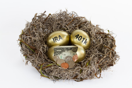 Nest full of golden eggs with one egg open containing cash and two eggs labeled 401k  IRA. Stock Photo