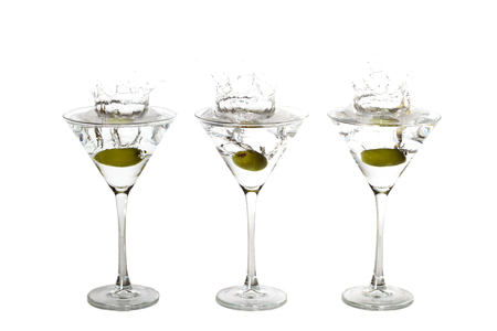 glases: Olives splashing into three martini glases at the same time.