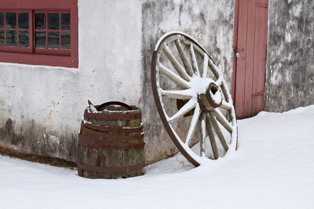 wheel barrel: Wagon wheel & barrel outside an old blacksmiths shop at Hopewell Furnace National Historic Site Stock Photo