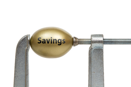 nest egg: A golden nest egg with Savings text  squeezed between a metal clamp. Stock Photo