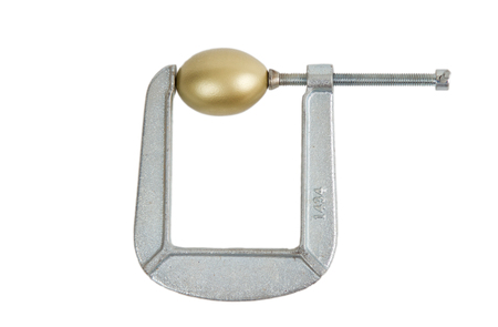 golden egg: Golden egg being squeezed in a metal clamp under pressure.