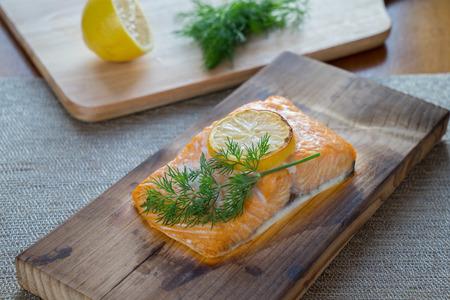 Fresh salmon on cedar plank with dill and lemon. 스톡 콘텐츠