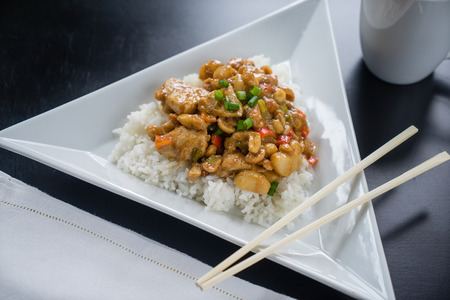 chopsticks: Plate of Kung Pao Chicken on white plate with chopsticks.