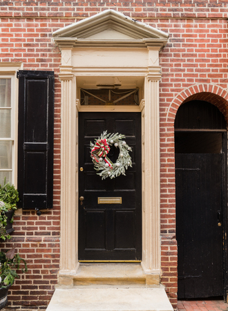 Colonial red doorway in historic Elfreths Alley in Philadelphia with pediment and  christmas wreath