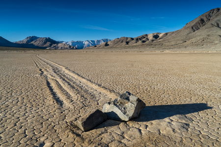 The Racetrack Playa, or The Racetrack, is a scenic dry lake feature with sailing stones that inscribe linear racetrack imprints. It is located above the northwestern side of Death Valley, in Death Valley National Park, Inyo County, California, U.S.