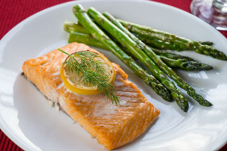 Grilled salmon, dill  and lemon on a white plate with asparagus