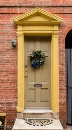 pediment: Colonial green doorway in historic Elfreths Alley in Philadelphia with pediment and  christmas wreath.