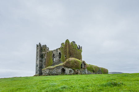 county kerry: Ballycarbery Castle is a castle near  Cahersiveen, County Kerry, Ireland. The castle is situated high on a grass hill facing the sea.   The present ruins were constructed in the 16th century.