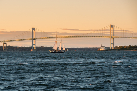 Sailboat passes the Claiborne Pell Bridge in Newport, Rhode Island with Rose Island lighthouse in the background